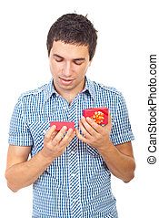 Young man looking into a open small gift