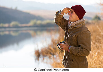 young man looking into distance - happy young man holding...