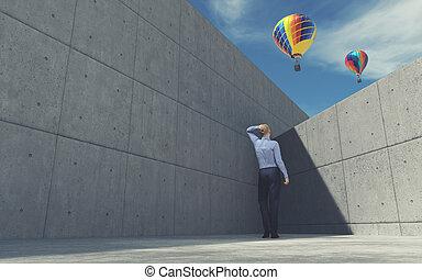 Young man looking over wall at air balloon