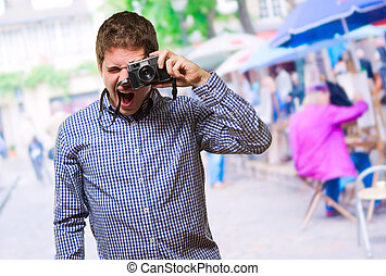 Young Man Looking Through A Vintage Camera
