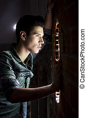 Young man looking through hole in brick wall