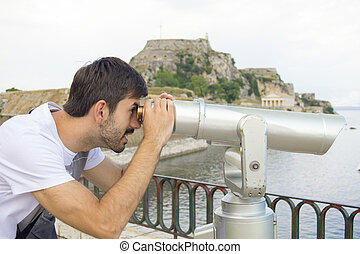 Young man looking through the public binoculars on a cloudy day