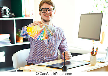 Young man looking to a color paint palette