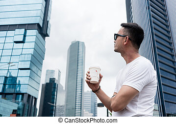 Young man looking up to the skyscrapers of a modern business dis