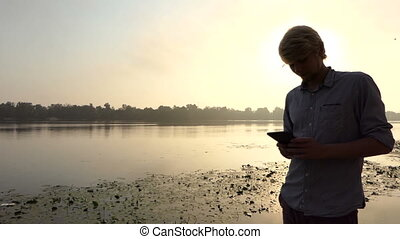 Young Man Looks at His Smartphone And Smiles at Sunset at the Dnipro