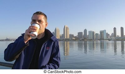 Young man looks at the camera and drink coffee - Young manly...