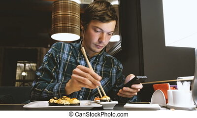 young man looks at the screen of a modern smartphone that is gaining the message and eating sushi in a Japanese restaurant