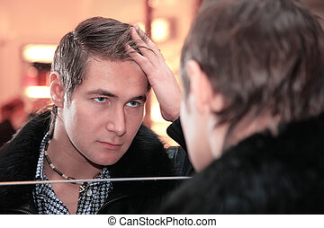 young man looks in mirror