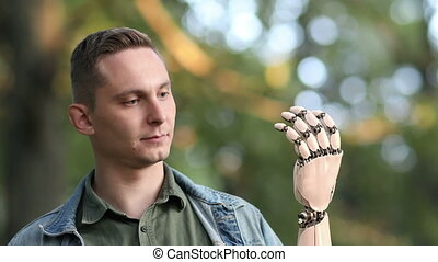 Young Man Looks on His Robotic Hand
