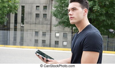 Young man lost in city, looking up directions on tablet PC