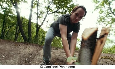 Young man lumberjack chopping wood in the forest