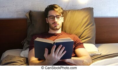 Young man lying in bed and reading a book