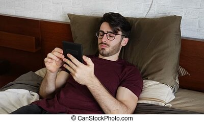 Young man lying in bed and reading ebook