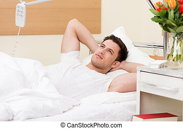 Young man lying in bed daydreaming
