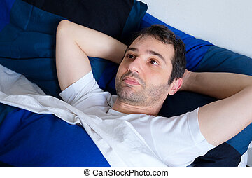 Young man lying in the bed feeling bad and trying to sleep in the morning