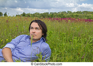 Young man lying on a spring meadow