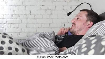 Young man lying on bed talking on mobile