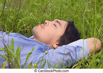 Young man lying on green grass