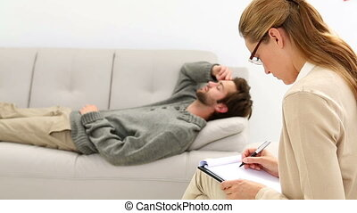 Young man lying on sofa talking to therapist