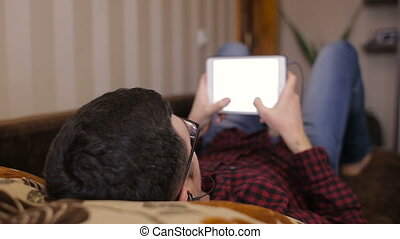 Young man lying on the couch and gaining a sms on a tablet and listening to music