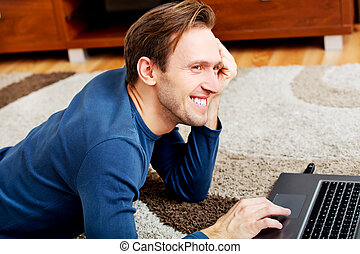 Young man lying on the floor and using laptop