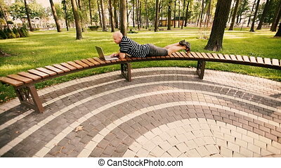 Young man lying on the park bench