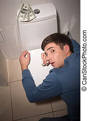 young man lying on toilet seat. drug addict kneeling over toilet seat with dollars
