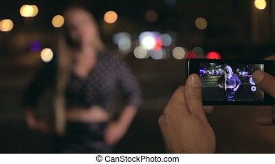 Young man makes photos of his girlfriend at night