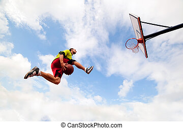 Young man making a fantastic slam dunk playing streetball,...