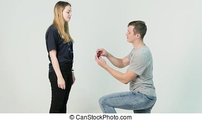 Young man making marriage proposal to his girlfriend. Man is...