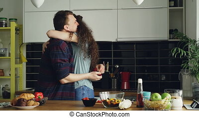 Young man making proposal to his girlfriend while she cooking in the kitchen at home. He putting ring on her finger and kissing her