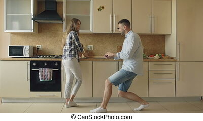 Young man making proposal to his girlfriend in the kitchen at home