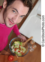 Young man making salad in the kitchen