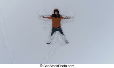 Young man making snow angels, aerial