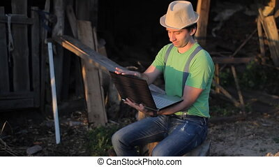 Young man making video call at the sawmill with laptop computer in his hands