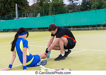 Young man massaging woman's injured leg