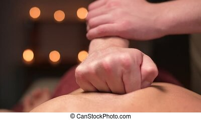 Close-up Young male masseur doing sports massage to a muscular athlete. Professional back massage in a dark room with candles. Relaxation and spa recovery of the muscular apparatus.