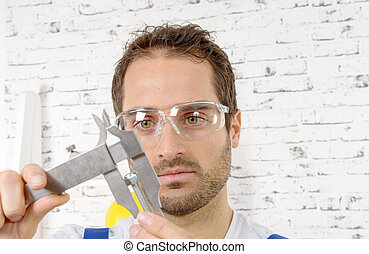 young man measuring screw using caliper