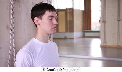 young man meditates in the gym