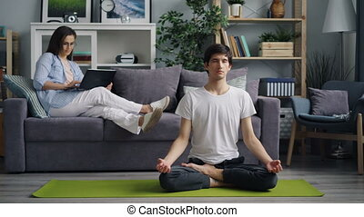 Young man meditating on yoga mat while woman working with laptop smiling