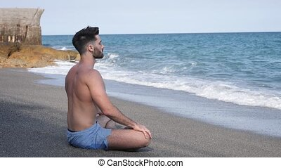 Young Man Meditating or Doing Yoga Exercise by Sea