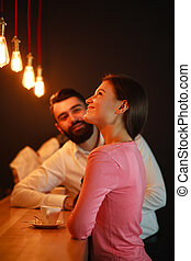 Young man met behind the bar with girl in a nightclub