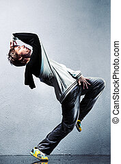 Young man modern dance. On wall background.