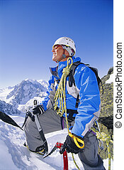 Young man mountain climbing on snowy peak