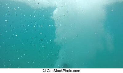 Young man moves down in see-through sea waters with bubble...