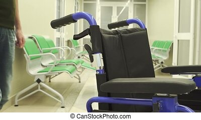 Young man moves wheelchair in premise in hospital. He holds...