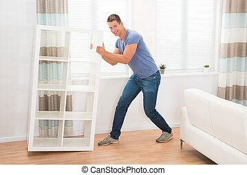 Young Man Moving Shelf