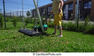 Young man mows lawn with electrical mower in children...