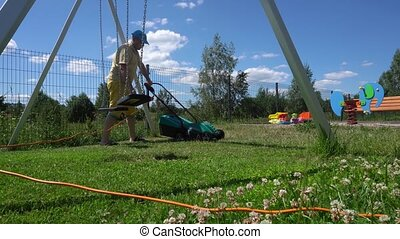 Young man mows the lawn with in children playground. Gimbal...