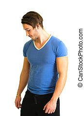 Young man, muscular build, standing and looking down